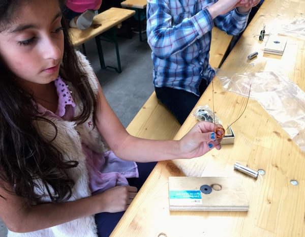 Young girl winding a coil